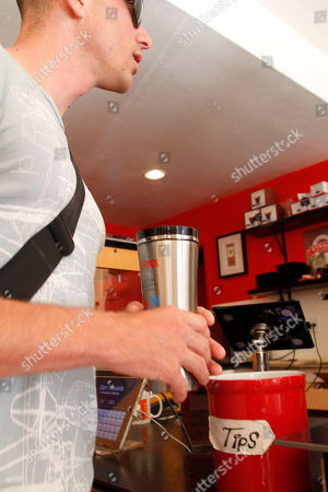 "Stock Photo of John Davison receives his ""free fill"" of coffee on the inaugural ""National Fill Your Thermos Brand Bottle Day,"" at Contraband Coffee Bar in San Francisco. This event is being held in select cities and coffee shops throughout the nation, hosted by the iconic Genuine Thermos Brand, to kick off the holiday weekend"