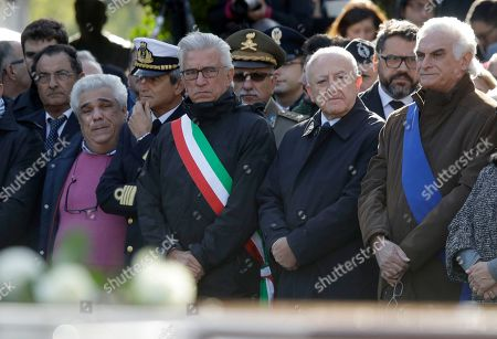 Mayor of Salerno Vincenzo Napoli, wearing a sash with the colors of the Italian flag, and President of the Campania Region Vincenzo De Luca, second from right, attend the funeral service for 26 Nigerian women, at the Salerno cemetery, southern Italy, Friday Nov.17, 2017. The women died last week while crossing the Mediterranean sea in an attempt to reach Italy