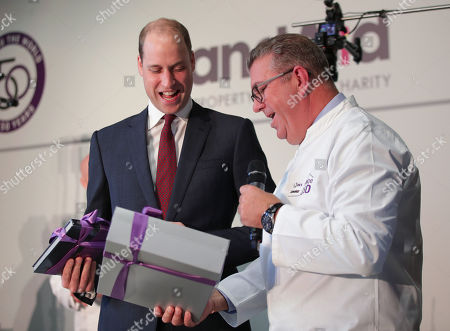 Prince William is presented with a gift of little chef outfits for Prince George and Princess Charlotte from Sean Tompkins (right), CEO of RICS, during the launch of LandAid's Pledge150 campaign, at the RICS