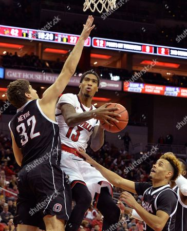 Ray Spalding, Daniel Norl, Daniel Meyer. Louisville forward Ray Spalding (13) attempts a layup through the defense of Omaha forward Daniel Meyer (32) and guard Daniel Norl (13) during the second half of an NCAA college basketball game, in Louisville, Ky