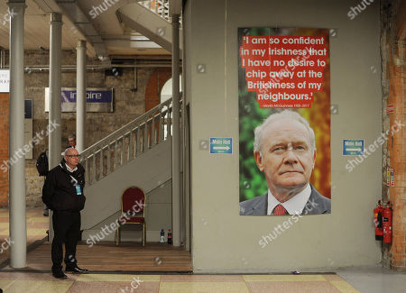 A security guard stands beside a photograph showing late Sinn Fein politican Martin McGuinness, who died earlier this year, at the 2017 Sinn Fein Ard Fheis annual party conference in Dublin, Ireland, 18 November 2017. It is expected that Sinn Fein president Gerry Adams will announce his retirement at his leader's speech.