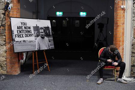 A Sinn Fein delegate sits beside a photograph showing late Sinn Fein politican Martin McGuinness, who died earlier this year, at the 2017 Sinn Fein Ard Fheis annual party conference in Dublin, Ireland, 18 November 2017. It is expected that Sinn Fein president Gerry Adams will announce his retirement at his leader's speech.