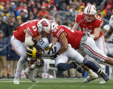 Michigan's Chris Evans is stopped by Wisconsin's Ryan Connelly (43), T.J. Edwards and Andrew Van Ginkel during the second half of an NCAA college football game, in Madison, Wis