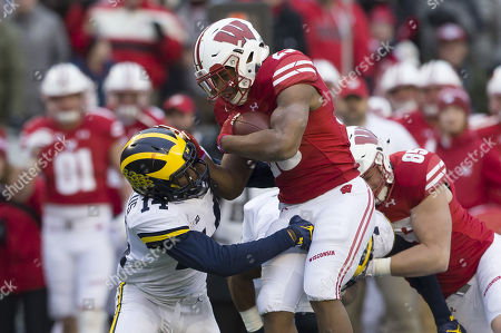 Wisconsin Badgers running back Jonathan Taylor #23 runs over Michigan Wolverines defensive back Josh Metellus #14 during the NCAA Football game between the Michigan Wolverines and the Wisconsin Badgers at Camp Randall Stadium in Madison, WI. Wisconsin defeated Michigan 24-10