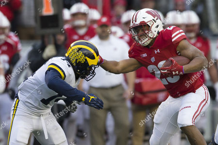Wisconsin Badgers running back Jonathan Taylor #23 stiff arms Michigan Wolverines defensive back Josh Metellus #14 during the NCAA Football game between the Michigan Wolverines and the Wisconsin Badgers at Camp Randall Stadium in Madison, WI. Wisconsin defeated Michigan 24-10
