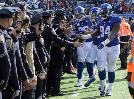 Dalvin Tomlinson, Olivier Vernon, Evan Engram. New York Giants defensive tackle Dalvin Tomlinson (94), defensive end Olivier Vernon (54) and tight end Evan Engram greet New York City police officers (88) before an NFL football game against the Kansas City Chiefs, in East Rutherford, N.J