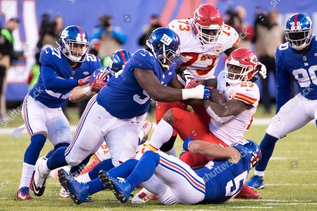 , 2017, Kansas City Chiefs running back Kareem Hunt (27) gets stopped by New York Giants defensive tackle Dalvin Tomlinson (94) and defensive end Olivier Vernon (54) during the NFL game between the Kansas City Chiefs and the New York Giants at MetLife Stadium in East Rutherford, New Jersey. The New York Giants won 12-9