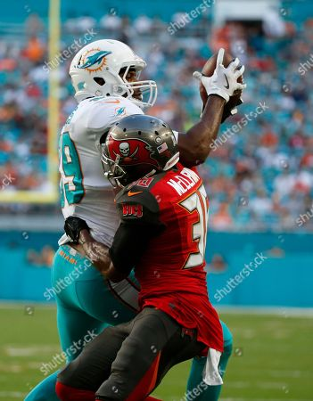 Julius Thomas, Robert McCain. Miami Dolphins tight end Julius Thomas (89) grabs a pass over Tampa Bay Buccaneers defensive back Robert McClain (36), during the second half of an NFL football game, in Miami Gardens, Fla