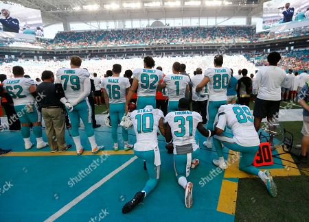 Kenny Stills, Michael Thomas, Julius Thomas. Miami Dolphins wide receiver Kenny Stills (10), free safety Michael Thomas (31) and tight end Julius Thomas (89), kneel during the National Anthem behind their teammates before an NFL football game against the Tampa Bay Buccaneers, in Miami Gardens, Fla