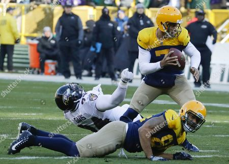 Green Bay Packers quarterback Brett Hundley gets away from Baltimore Ravens' Carl Davis during the first half of an NFL football game, in Green Bay, Wis