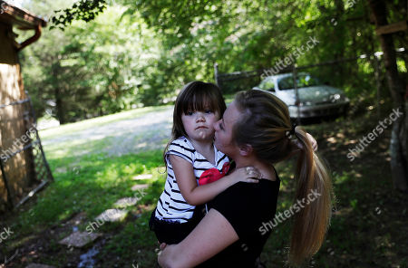 """Stock Picture of Whitney Duncan holds her daughter, Deklyn, 3, while visiting her at the home she's staying at with her grandmother in Jasper, Ga., . Duncan and her husband were given a choice after failing a drug screening in 2016; lose their daughter to foster care or temporarily give her to a family member while they enter the county's two-year family drug court program to help with their opioid addiction. """"Knowing that I couldn't go pick her up when I wanted to, that I wasn't go to be able to be with her at night time and that my whole world had changed and just realizing what I had done, that was my rock bottom,"""" said Duncan"""