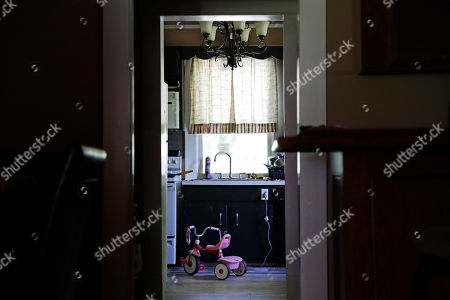 """A tricycle belonging to their daughter sits in the kitchen of Whitney and Dalton Duncan's home in Jasper, Ga., . They were given a choice after failing a drug screening in 2016; lose their daughter to foster care or temporarily give her to a family member while they enter the county's two-year family drug court program to help with their opioid addiction. """"At home when she's not there you feel empty. The house feels empty,"""" said Whitney Duncan. """"It's just so quiet. You don't want to be there. It's depressing"""