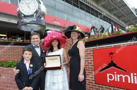 Juan-Carlos Capelli, left, with his son Thomas, and Jennifer Judkins, right, both of Longines, present Holly Huff, of Crofton, MD, with a Longines St. Imier steel and rose gold diamond timepiece after she won the Longines Most Elegant Woman at Preakness Fashion Contest, at Pimlico Race Course in Baltimore, MD. Longines, the Swiss watch manufacturer known for its luxury timepieces, is the Official Watch and Timekeeper of the 138th annual Preakness Stakes