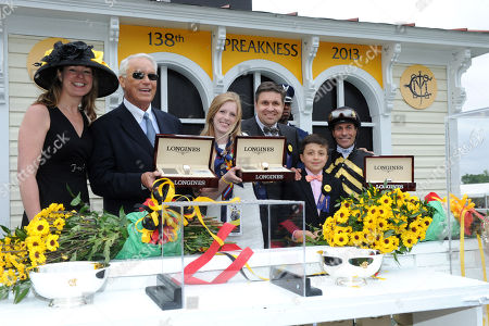 Juan Carlos-Capelli, center, with his son Thomas, and Jennifer Judkins, left, both of Longines, award trainer D. Wayne Lukas, second left, jockey Gary Stevens, right, and Erin Kelley, daughter of owner Brad Kelley, with their Longines St. Imier chronographs after their horse Oxbow won the 138th Preakness Stakes, in Baltimore, MD. Longines, the Swiss watchmaker known for its famous timepieces, is the Official Watch and Timekeeper of the 138th annual Preakness Stakes