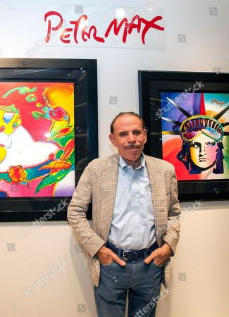 Artist Peter Max poses for a photo during his retrospective with the Road Show Company exhibit in Northbrook Court mall in Northbrook, Ill. Since he charged onto the pop-art stage a half-century ago, the progenitor of psychedelic art has stamped his creative presence on practically everything from the sides of an airliner and the hull of a Norwegian Cruise Lines ship to commemorative U.S. postage stamps and, most lately, an endless string of art galleries stretching from one end of the United States to the other