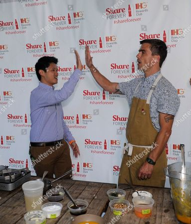 Chef Hugh Acheson, right, high fives with Timothy Lin after a food demonstration at the IHG Rewards Club Share Forever exclusive member event at Empire State South restaurant, in Atlanta