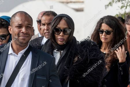 Naomi Campbell, center, and Tunisian-born fashion model Afef Jnifen, right, attend the funeral ceremony of Tunisian-born designer Azzedine Alaia in Sidi Bou Said, north of the Tunisian capital Tunis, . Azzedine Alaia, an iconoclast whose clingy dresses marked the 1980s and who dressed famous women from Hollywood to the White House, has died at age 77