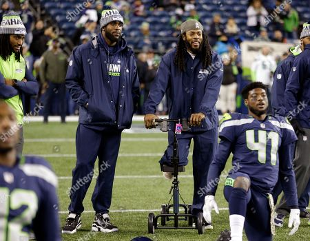 Kam Chancellor, Richard Sherman. Seattle Seahawks Kam Chancellor, left, and Richard Sherman, both out injured, look on at teammates stretching before an NFL football game against the Atlanta Falcons, in Seattle