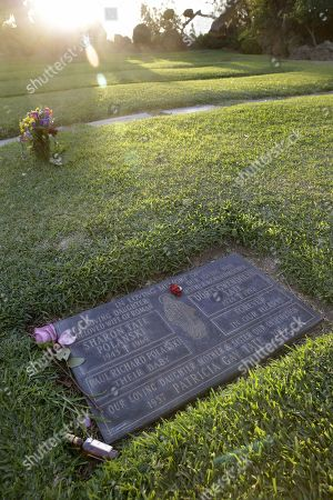 Flowers and a bottle of alcohol are placed next to the grave of US actress Sharon Tate and her unborn child, who were murdered by Charles Manson's followers in August 1969, buried in the Holy Cross Cemetery in Culver City, California, USA, 20 November 2017. Charles Manson, cult leader and convicted murderer, has died aged 83 in a prison on 19 November 2017. The grave is the Tate family burial plot where Sharon Tate, her unborn son Paul, mother Doris, and sister Patti are placed.