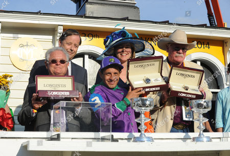 Charles Villoz, back row left, and Jennifer Judkins, back row center, both of Longines, present trainer Art Sherman, left, jockey Victor Espinoza and co-owner Steve Coburn with Longines Conquest Classic timepieces after their horse California Chrome won the 139th Preakness Stakes and the second leg of the Triple Crown, in Baltimore, MD. Longines, the Swiss watchmaker known for its famous timepieces, is the Official Watch and Timekeeper of the 139th annual Preakness Stakes and the Triple Crown