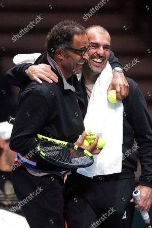 French Captain Yannick Noah, left, and former french player Cedric Pioline smile during a training session at the Pierre Mauroy stadium in Lille, northern France, . France will face Belgium in the Davis Cup final starting next Friday