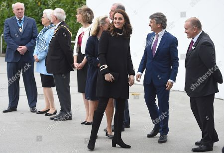Stock Image of Catherine Duchess of Cambridge is greeted by dignatories including CEO of Jaguar Land Rover Ralf Speth (2R) as she arrives for a visit to Jaguar Land Rover's Solihull manufacturing plant