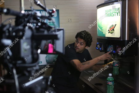 """IMAGE DISTRIBUTED FOR MOUNTAIN DEW - Professional skateboarder Paul """"P-Rod"""" Rodriguez fills up bottles of Mtn Dew Baja Blast from a Taco Bell® fountain while filming the Mtn Dew Baja Blast """"Baja Breakout"""" video, on Thurs., in Los Angeles. Rodriguez appears in the short film, debuting today, Mon., May 6, 2014, along with racing champion Dale Earnhardt Jr. and professional snowboarder Danny Davis. Mountain Dew recently announcing that, for the first time, Mtn Dew Baja Blast - which was introduced 10 years ago as a """"Taco Bell® Original"""" - will also be available for a limited time in bottles and cans. The tropical lime flavored beverage started hitting shelves on Mon., May 5, 2014"""