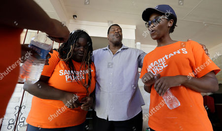 George Dorsey, Nikki Moore, Samantha Roundtree. George Dorsey, center, prays with Samaritan's Purse volunteers, Nikki Moore, left, and Samantha Roundtree, who are helping to rebuild his hurricane-damaged home in Houston. Dorsey usually hosts a large Thanksgiving dinner for family but is making other arrangements this year as he and his wife continue to recover from Hurricane Harvey