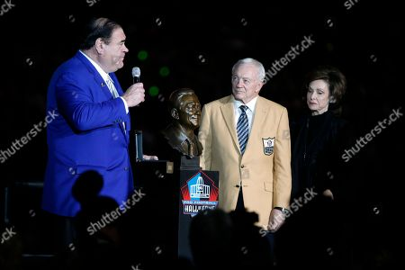 Pro Football Hall of Fame president David Baker (left) talks as Dallas Cowboys owner Jerry Jones (center) and wife Gene Jones (right) listen during his HOF ring presentation at halftime of an NFL football game, in Arlington, Texas