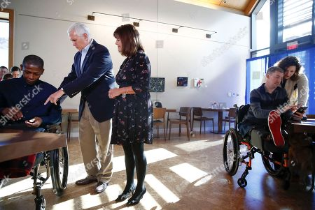 Mike Pence, Karen Pence, David Mathis, Jr., Liam Dwyer, Meghan. Vice President Mike Pence and his wife Karen Pence talk with Sgt. David Mathis, Jr., 40, of the G Forward Support Company, Fort Polk, La., left, as Staff Sgt. Liam Dwyer, 36, of the 3rd Battalion 5th, Marine Regiment, Camp Pendleton, right, and his wife Meghan look at the photos they just took with the Pence's at the USO Warrior and Family Center at Walter Reed National Military Medical Center in Bethesda, Md