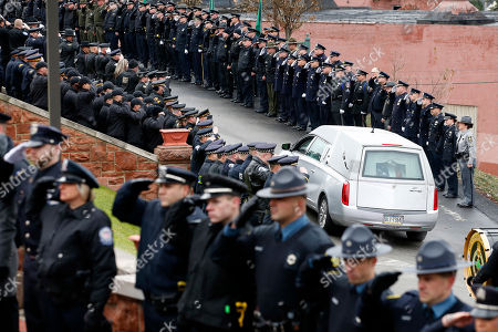 Thousands of police officers attend the funeral for slain New Kensington Police Officer Brian Shaw as the hearse makes its way up to Mount St. Peter Church in New Kensington, Pa., . Shaw was shot and killed during a traffic stop on Friday night