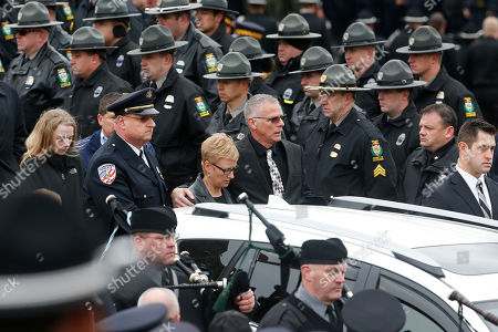 Family members and friends exit the funeral for slain New Kensington Police Officer Brian Shaw at Mount St. Peter Church in New Kensington, Pa., . Shaw was shot and killed during a traffic stop on Friday night