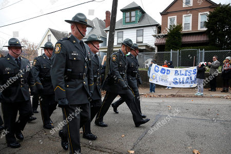 Pennsylvania State Troopers walk the procession on their way to the cemetery as local residents hold up a sign following the funeral for slain New Kensington Police Officer Brian Shaw at Mount St. Peter Church in New Kensington, Pa., . Shaw was shot and killed during a traffic stop on Friday night