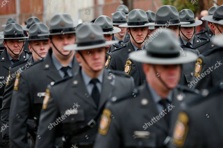 Pennsylvania State Troopers walk the procession on their way to the cemetery following the funeral for slain New Kensington Police Officer Brian Shaw at Mount St. Peter Church in New Kensington, Pa., . Shaw was shot and killed during a traffic stop on Friday night