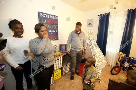 India Williams, second from left, reacts at Aaron's, Inc. and Warrick Dunn Charities Homes For The Holidays Presentation at India Williams' new home on in Tallahassee, Fla