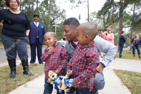 Warrick Dunn, center, with India Williams' twins pose for photos at the Aaron's, Inc. and Warrick Dunn Charities Homes For The Holidays Presentation at India Williams' new home on in Tallahassee, Fla