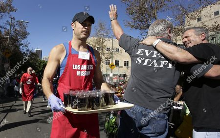US actor/model George Stults (L) carries a tray of sodas as part of Thanksgiving dinner plates served to homeless and less-fortunate people at the Los Angeles Mission in Los Angeles, California, USA 22 November 2017. It is estimated that over 60,000 people live on the streets in Los Angeles County with half of those in the city of Los Angeles.