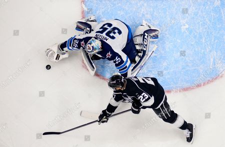 Dustin Brown, Steve Mason. Los Angeles Kings right wing Dustin Brown, right, tries to get a shot in on Winnipeg Jets goalie Steve Mason during the first period of an NHL hockey game, in Los Angeles