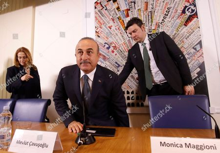 Turkish Foreign Minister Mevlut Cavusoglu arrives at the Foreign Press Club, followed by Italian journalist Monica Maggioni, left, in Rome