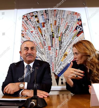 Turkish Foreign Minister Mevlut Cavusoglu listens to Italian journalist Monica Maggioni, right, as he attends a press conference at the Foreign Press Club, followed by left, in Rome