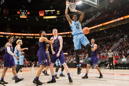 North Carolina forward Brandon Huffman, center, dunks over Portland forward Joseph Smoyer, left, during the second half in an NCAA college basketball game at the Phil Knight Invitation Tournament, in Portland, Ore