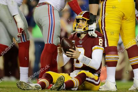 Washington Redskins quarterback Kirk Cousins (8) looks up after being sacked by New York Giants defensive tackle Dalvin Tomlinson (94) during the first half of an NFL football game in Landover, Md
