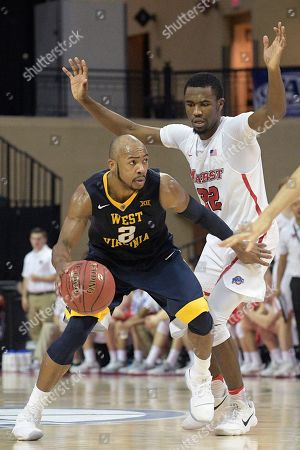 Jevon Carter, Austin Williams. West Virginia guard Jevon Carter (2) drives to the basket in front of Marist guard Austin Williams (22) during the second half of an NCAA college basketball game at the AdvoCare Invitational tournament, in Lake Buena Vista, Fla