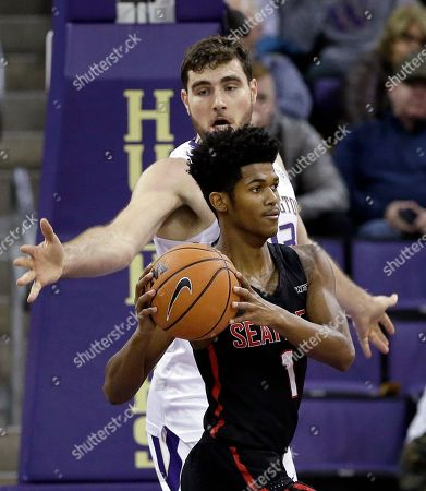 Stock Picture of Sam Timmins, Morgan Means. Seattle's Morgan Means (1) looks for room to pass as Washington's Sam Timmins defends in the first half of an NCAA college basketball game, in Seattle. Washington won 89-84