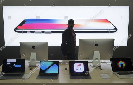 A customer walks past the image of the iPhone X on display beside computers and mobile devices at a Best Buy store on Black Friday in Alexandria, Virginia, USA, 24 November 2017. The day after Thanksgiving known as 'Black Friday'  kicks off the holiday season of shopping. Thirty percent of annual retail sales occur between Black Friday and Christmas, according to the National Retail Federation.