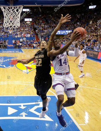 Stock Photo of Kansas' Malik Newman (14) shoots under pressure from Oakland's James Beck (22) during the first half of an NCAA college basketball game, in Lawrence, Kan