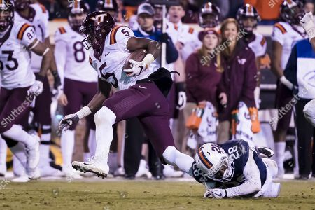 Virginia Tech Hokies wide receiver Cam Phillips (5) tries to break free from the diving tackle of Virginia Cavaliers safety Brenton Nelson (28) during the NCAA football game between the Virginia Tech Hokies and the Virginia Cavaliers at David A. Harrison III Field at Scott Stadium in Charlottesville, Virginia
