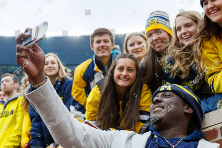 Stock Image of th, Former Michigan Wolverines quarterback Denard Robinson takes a selfie with fans during an NCAA football game between the Ohio State Buckeyes and the Michigan Wolverines at Ohio Stadium, Columbus, OH