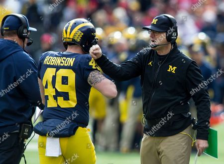 Stock Image of Jim Harbaugh, Andrew Robinson. Michigan head coach Jim Harbaugh, right, congratulates long snapper Andrew Robinson (49) after a Michigan touchdown in the first quarter of an NCAA college football game against Ohio State in Ann Arbor, Mich