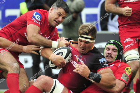 Southern Kings vs Scarlets. Southern Kings' Dries van Schalkwyk is tackled by Mike Phillips and Tom Price of Scarlets